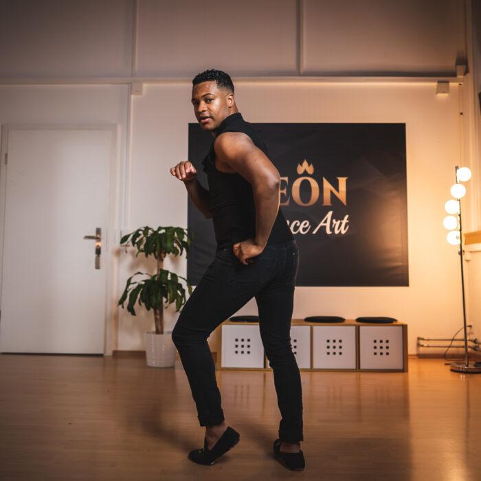 Mann zeigt Salsa Pose in der Tanzschule